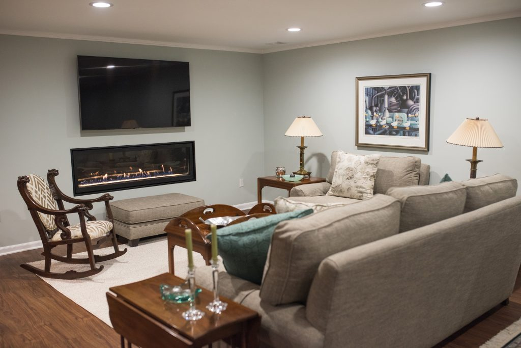 basement living room with sofas and electric fireplace and tv