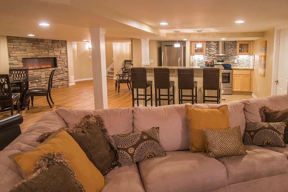 bright and open concept basement with sectional and kitchen