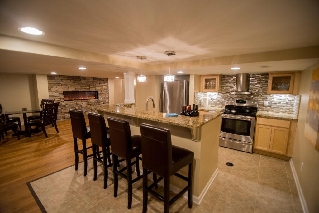 basement kitchen with stone fireplace and glass backsplash