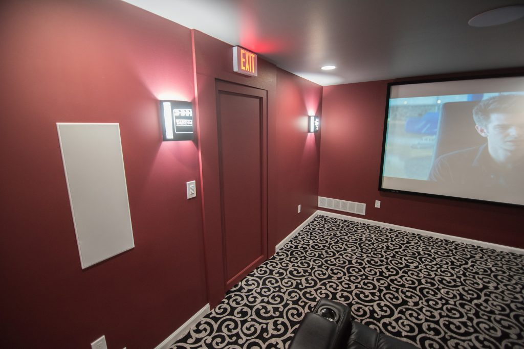 exit sign and sconce lighting in basement movie theater northville