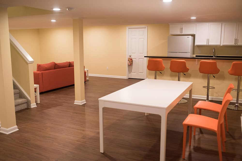 open concept living and dining space in basement with vinyl plank flooring
