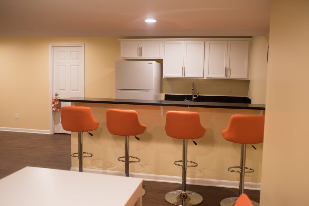basement bar with seating and granite countertops