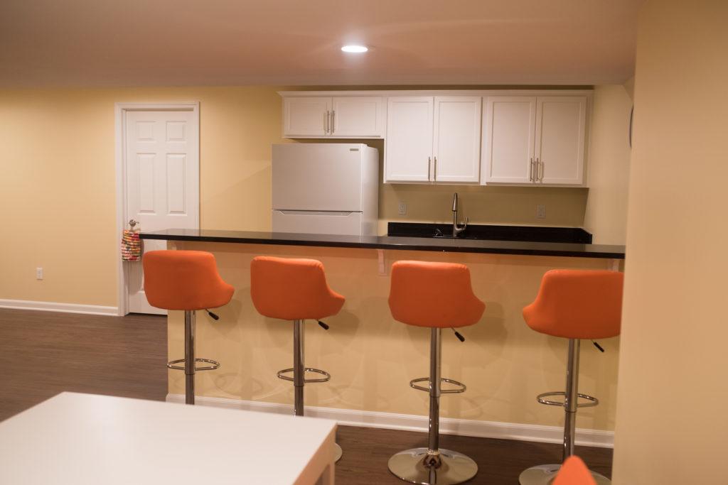 basement bar with seating and granite countertops
