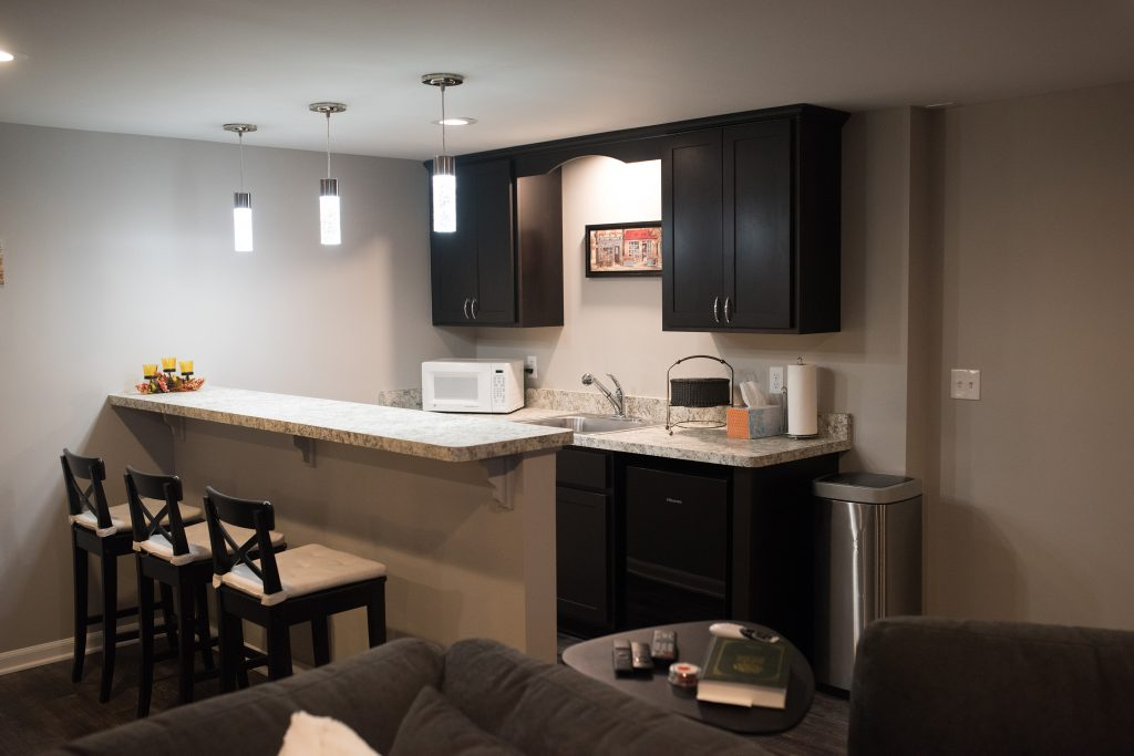 bar area in basement with dark cabinets and white laminate countertops