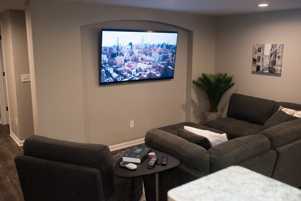 living room area in basement with tv archway