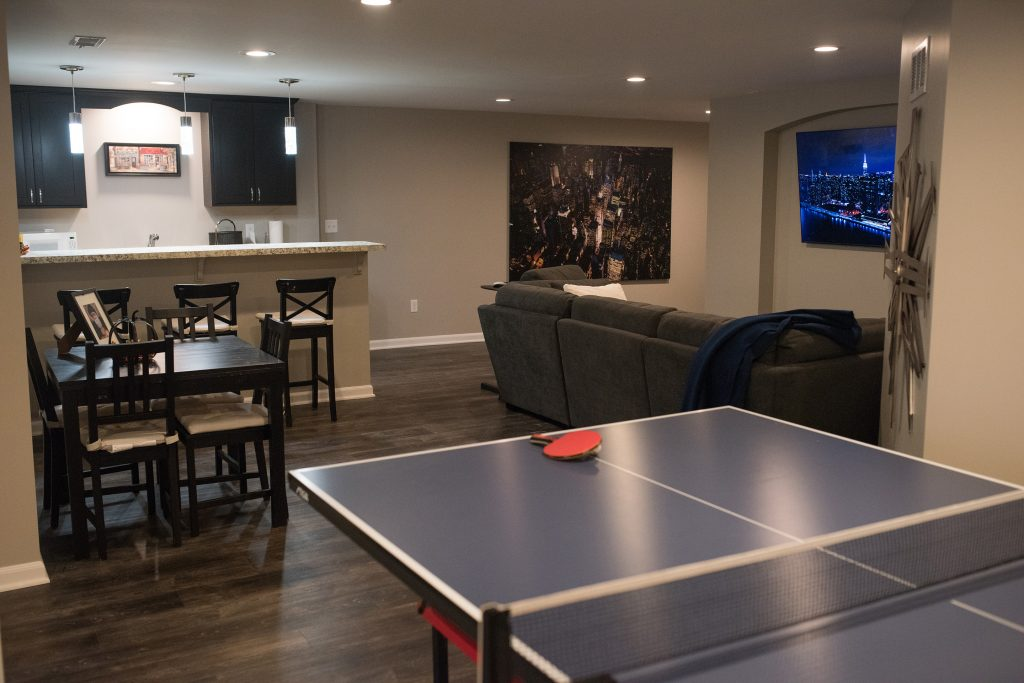 ping pong table in finished basement novi with dark vinyl plank flooring