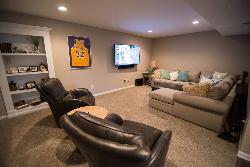 cozy basement living room with secret door and tv