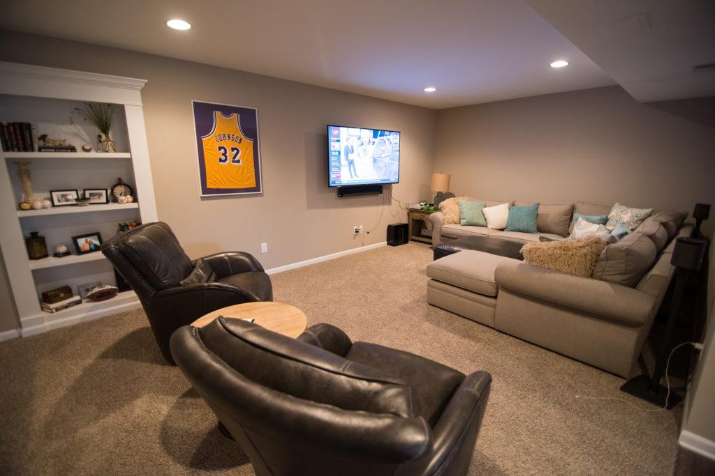 cozy basement living room with secret door and tv