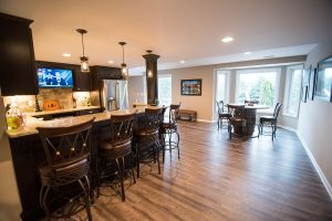 walkout basement with dark vinyl plank and custom bar