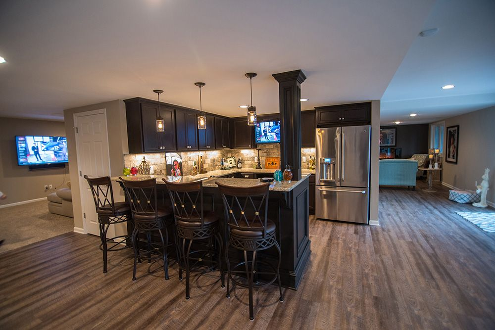 finished basement with bar and vinyl plank flooring