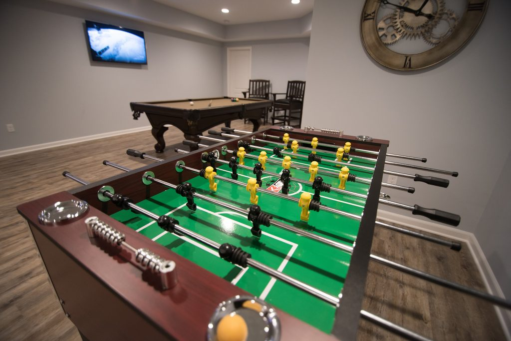 game area in finished basement with pool table and extra tv