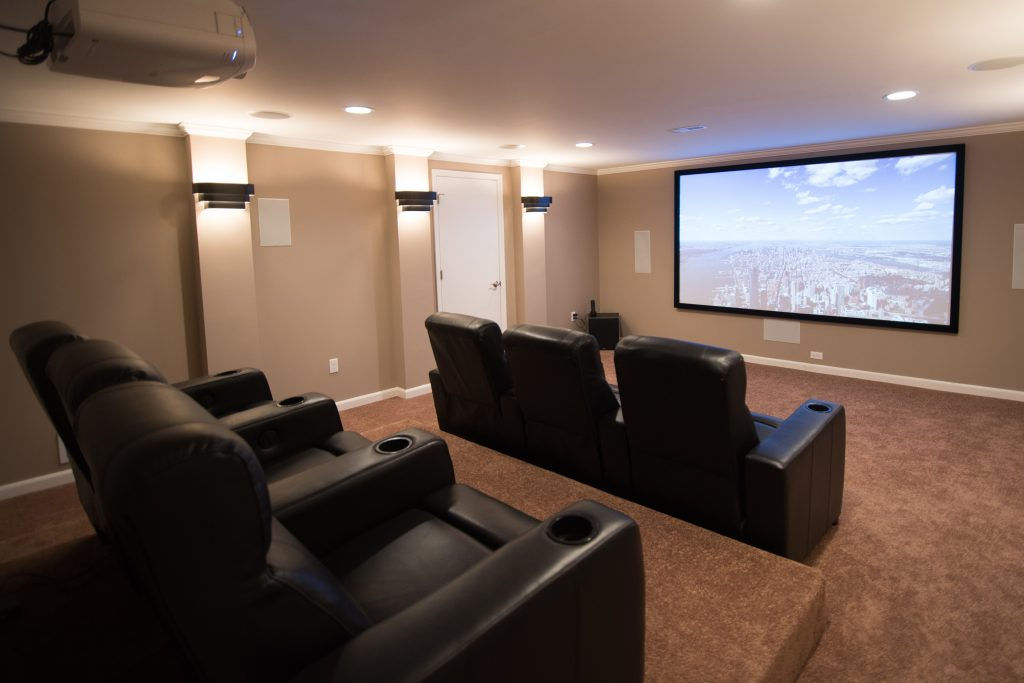 basement movie theater with projection screen recliners and platform seating