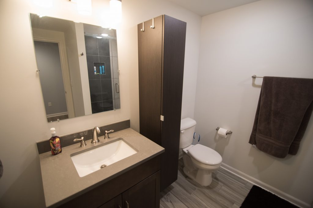 finished basement bathroom with shower and vinyl tile