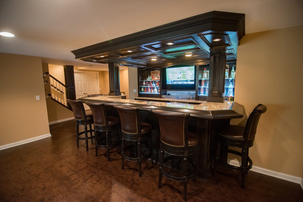 large home bar in basement with granite countertops