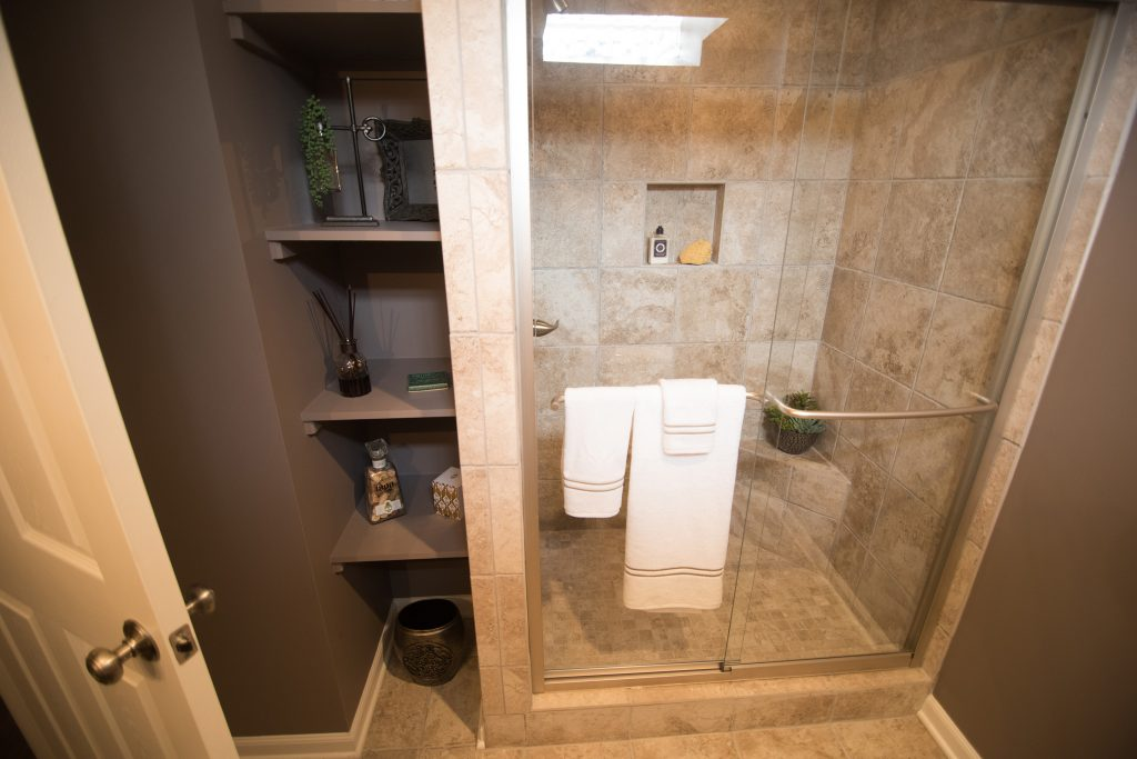 spare bathroom in basement with vinyl tile and custom sheliving