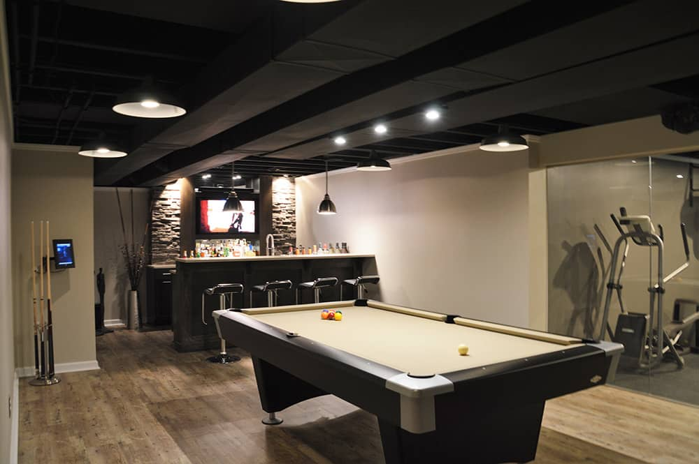 modern basement bar with black painted ceiling and stone bar