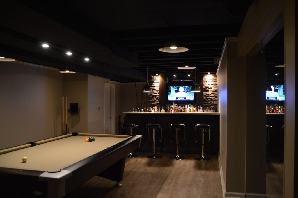 basement bar with dark features and modern design such as stone veneer