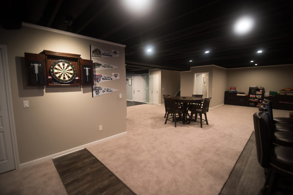 painted black ceilings in a modern basement with a dart board and carpeting