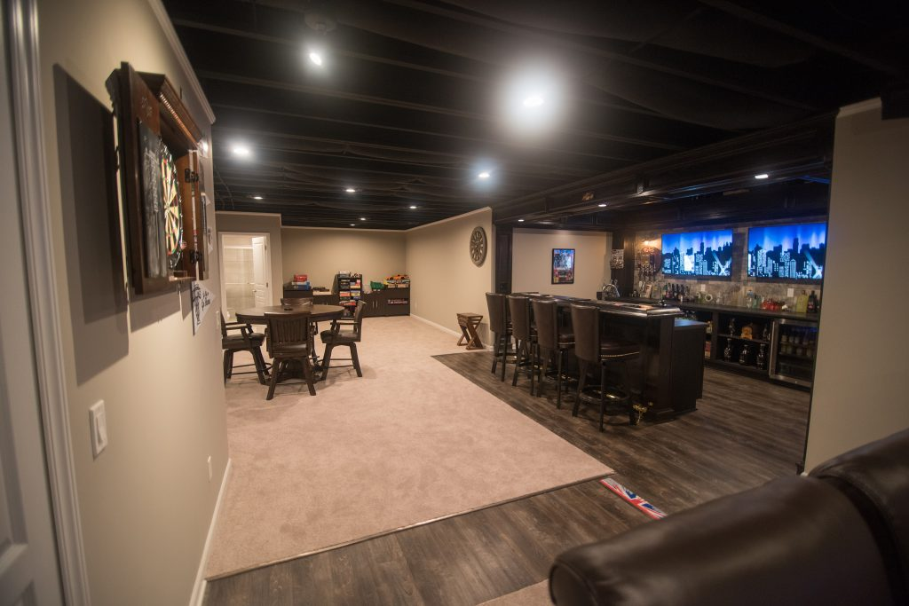 painted ceiling in basement with carpet and large custom bar