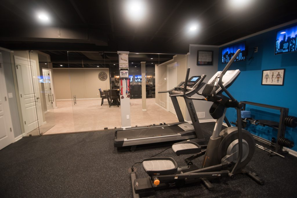 basement fitness room with rubber flooring and painted ceiling