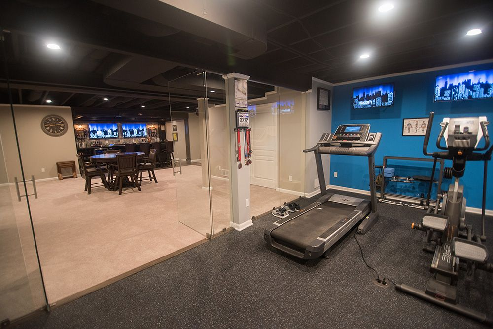 basement fitness room with rubber flooring and blue walls