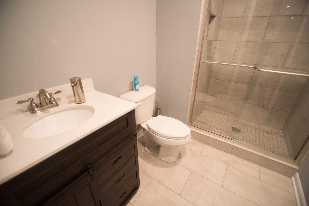 vinyl tile in basement bathroom with dark vanity with quartz countertops