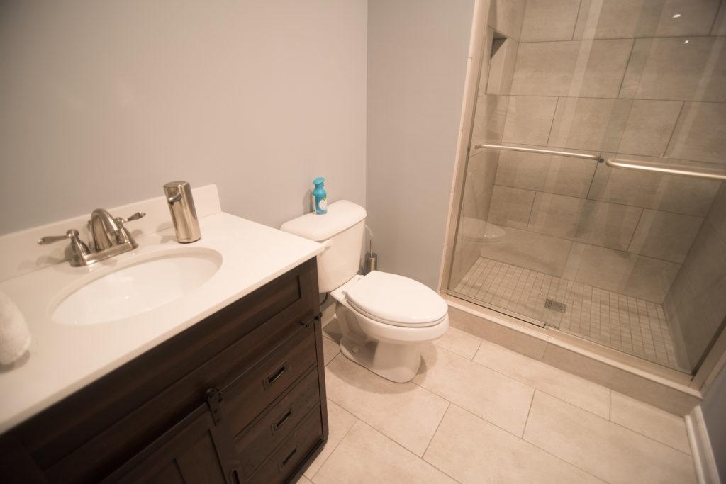 vinyl tile in basement bathroom with dark vanity with quartz countertops