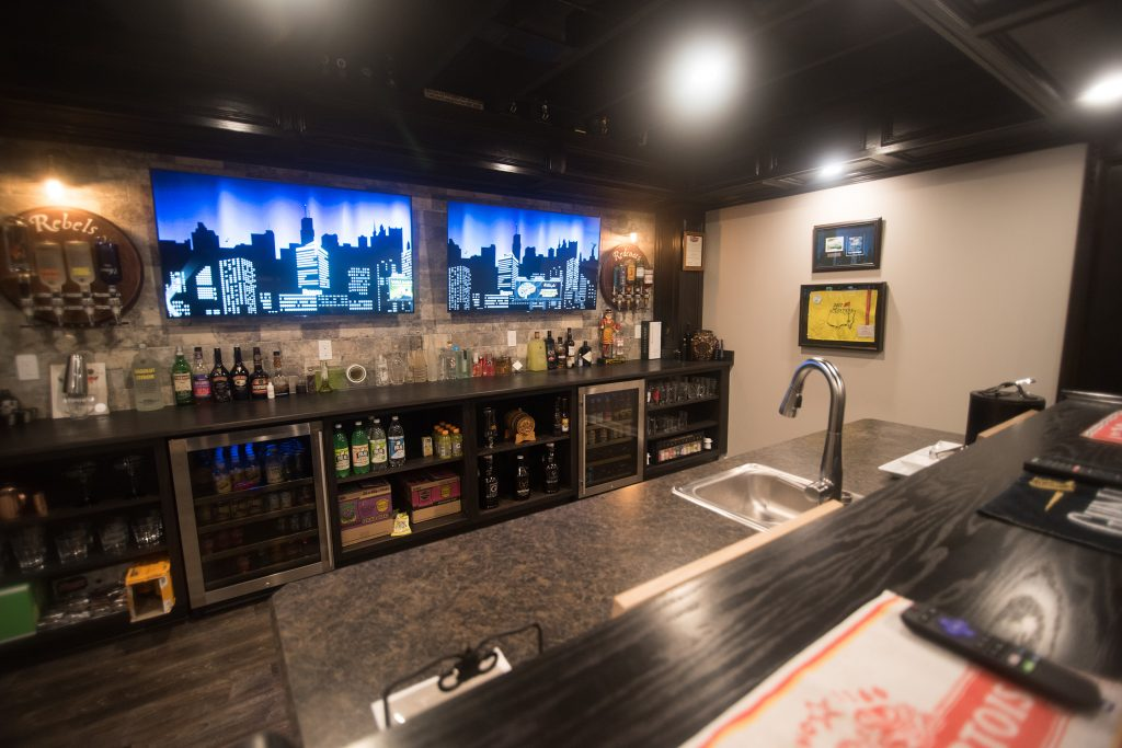 basement bar with dual tv screens and island with seating