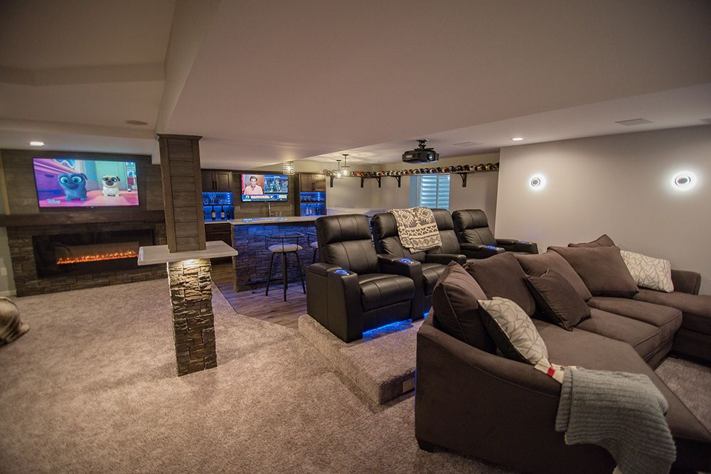large open finished basement with carpeting and theater with bar behind