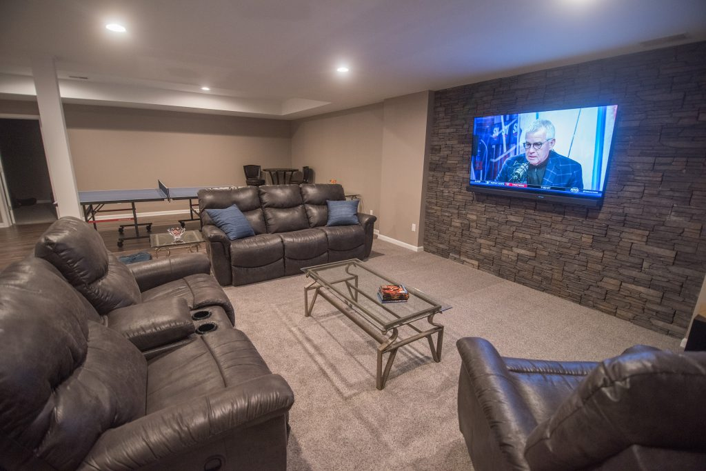 basement living room accent wall with stone and carpet