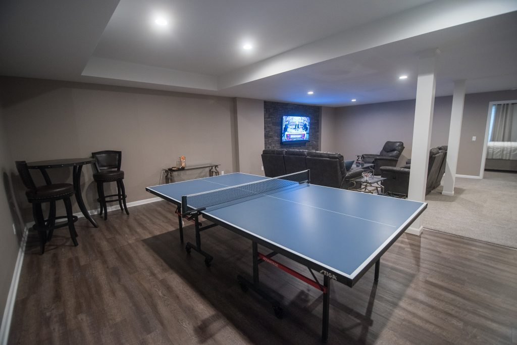 ping pong table next to living room with vinyl plank flooring