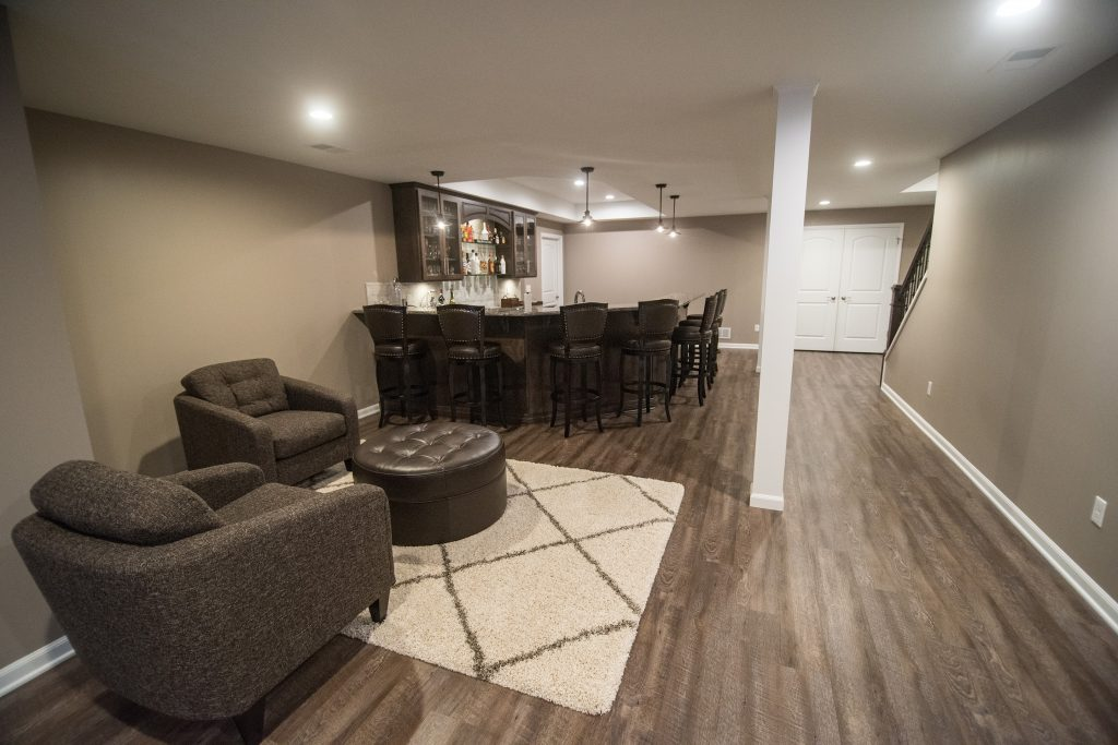 basement bar area with seating and vinyl plank flooring