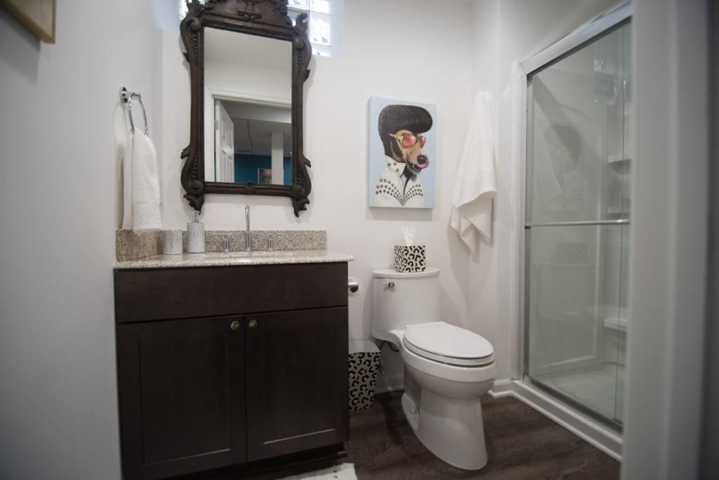 basement bathroom with dark vanity with granite top