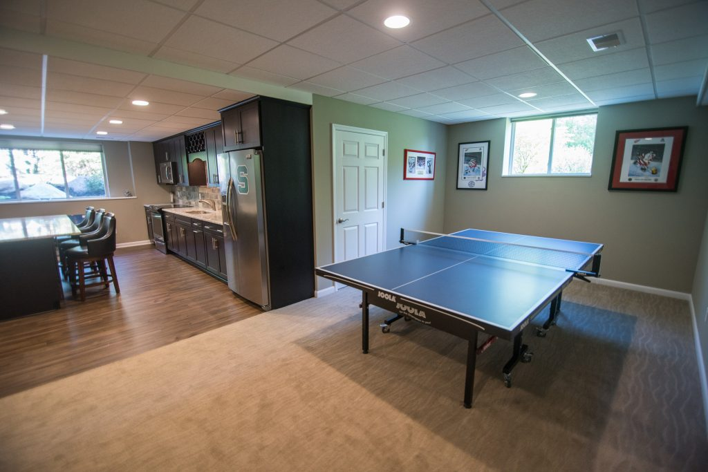 extra space in basement is being used for a pin pong table with carpet