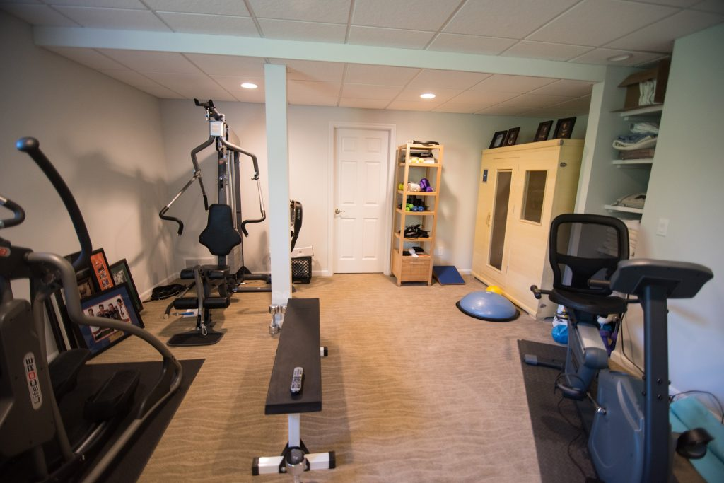 fitness room in basement with weight lifting equipment and a sauna