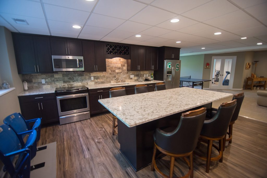basement kitchen with large granite island and dark maple cabinetry