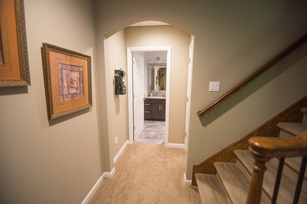 archway in basement leading to bathroom adding a design feature