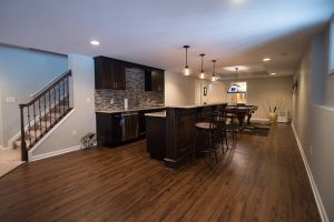 dark vinyl plank flooring in basement with traditional style bar