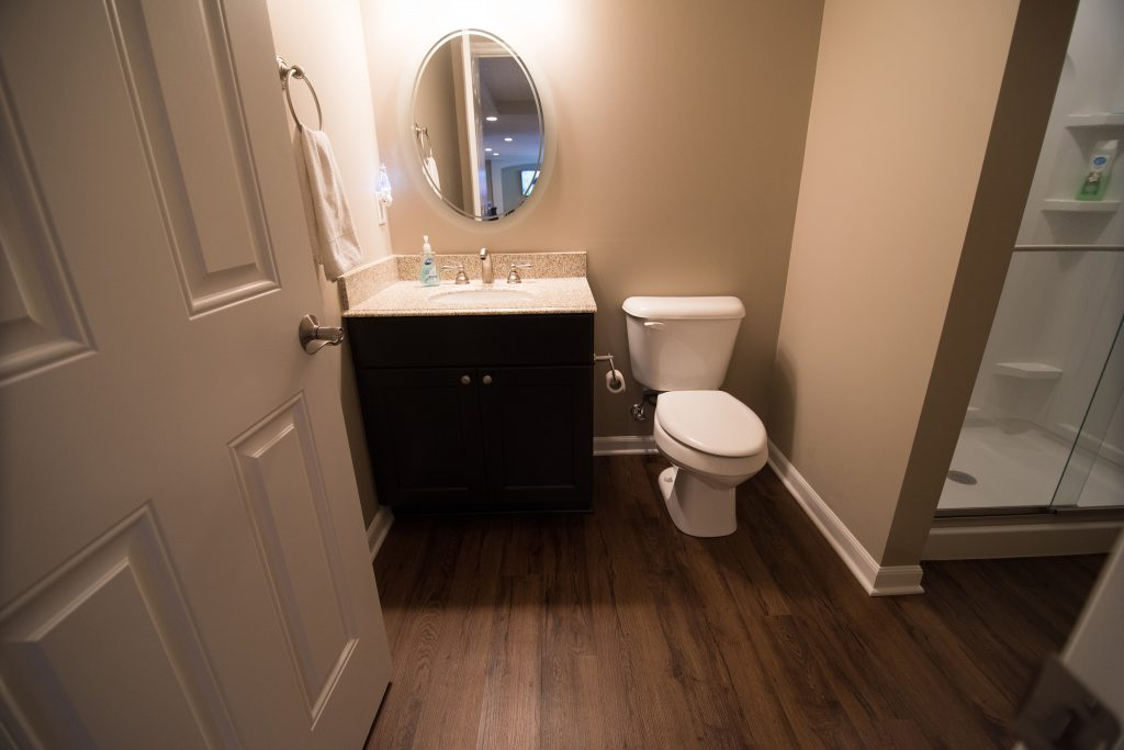 bathroom in finished basement with vinyl plank flooring and shower