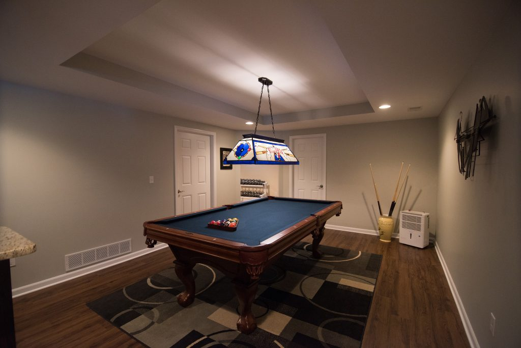 pool table with raised ceiling detail in finished basement