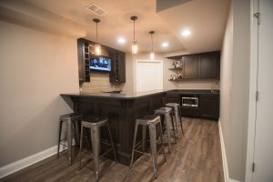 after image of basement with vinyl plank flooring and rustic design