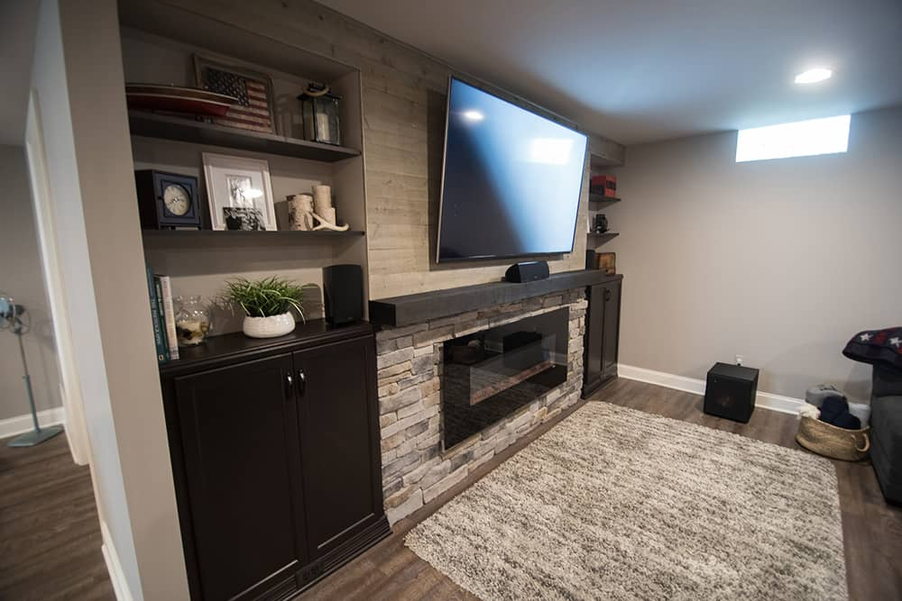 Tv wall in basement with wood beam and electric fireplace wrapped in stone in Wixom, Michigan