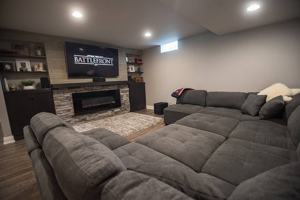 large sofa and tv wall with fireplace and stone