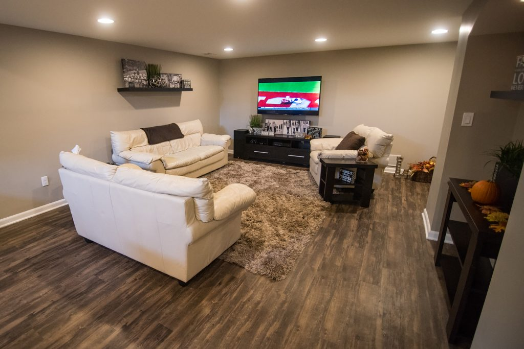 finished basement living room with dark vinyl plank flooring grey walls and white leather sofas