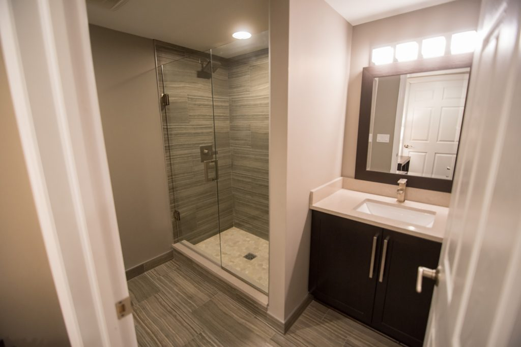 basement bathroom with tile flooring and matching shower
