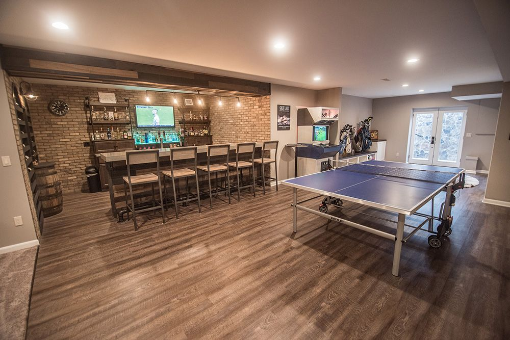 vinyl plank flooring with a ping pong table and bright industrial custom bar