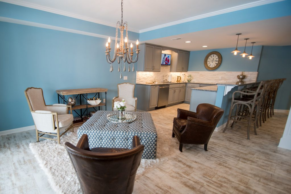 walkout basement with a seating area adjacent to the bar with large chairs and ottoman
