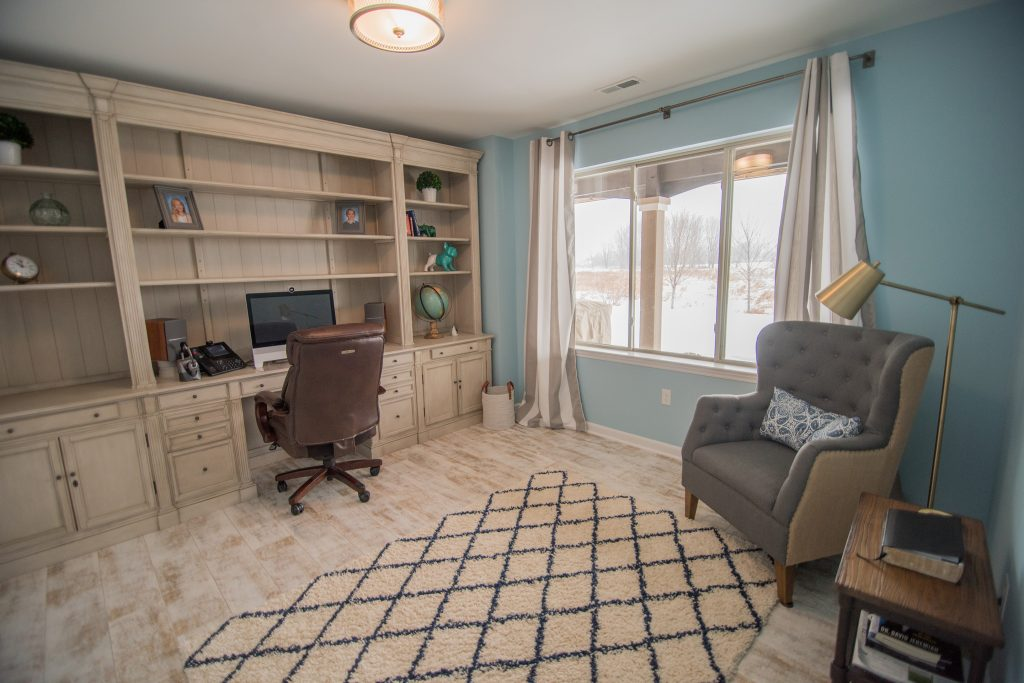 basement office with built in desk and large window