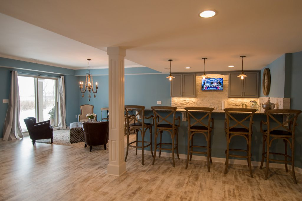 Bright open concept basement bar with light blue walls and beach style design