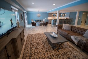 bright blue finished basement with walkout and vinyl plank flooring